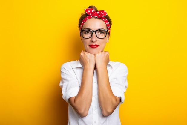 Junge frau hält ihre hände am kinn, trägt eine brille und ein stirnband an einer gelben wand. banner.