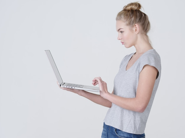 Junge frau hält laptop in habds. ruhiges kaukasisches mädchen mit notizbuch, das im studio aufwirft