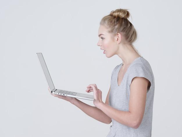Junge frau hält laptop in habds. schockiertes kaukasisches mädchen mit notizbuch, das im studio aufwirft