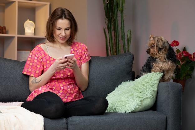 Junge frau hält smartphone mit blick auf handy-bildschirm lachend genießen mit mobilen apps zum einkaufen.