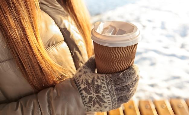 Junge frau hält tasse kaffee zum mitnehmen im winterpark