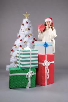 Junge frau hält umschlag auf grauem boden urlaub neujahr weihnachten
