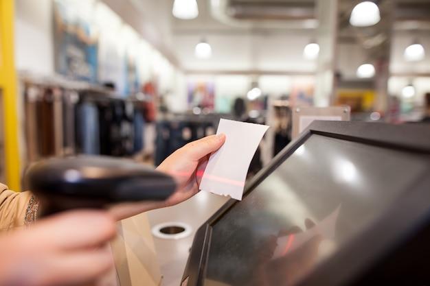 Junge frau hände, die eine rechnungszahlung für einen kunden am riesigen einkaufszentrum scannen
