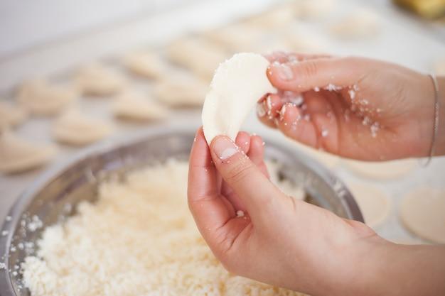 Junge frau hände, die einige ukrainische vareniks machen, handgemacht