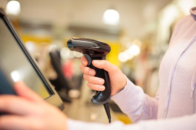 Junge frau hände, die scanner zum scannen von waren für einen kunden am riesigen einkaufszentrum verwenden