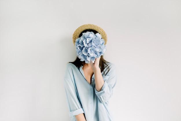 Junge frau halten blauen hortensienblumenstrauß auf weißer oberfläche