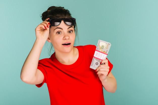 Junge frau halten gegen einen stapel geld lokalisiert auf blauem hintergrund