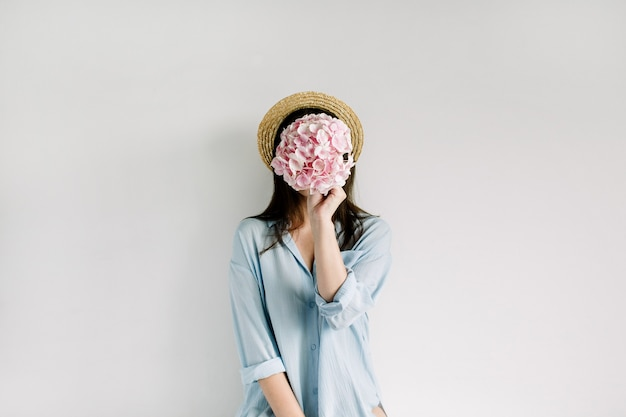 Junge frau halten rosa hortensienblumenstrauß auf weißer oberfläche