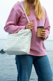 Junge frau halten stilvolle öko-tasche und pappbecher gegen meer
