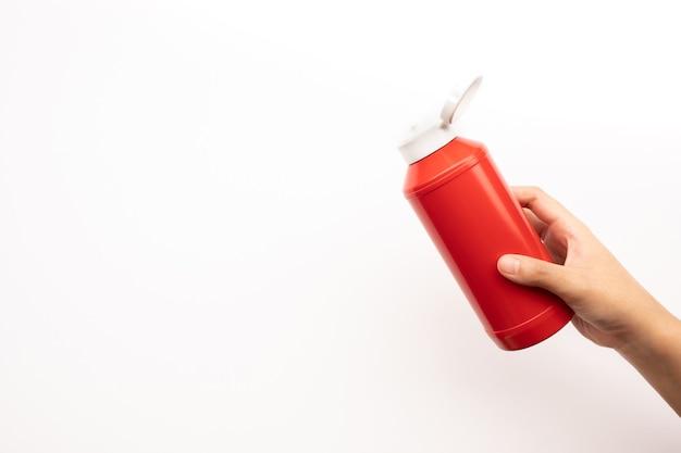 Junge frau hand quetschen flasche tomatensauce ketchup auf weißem hintergrund
