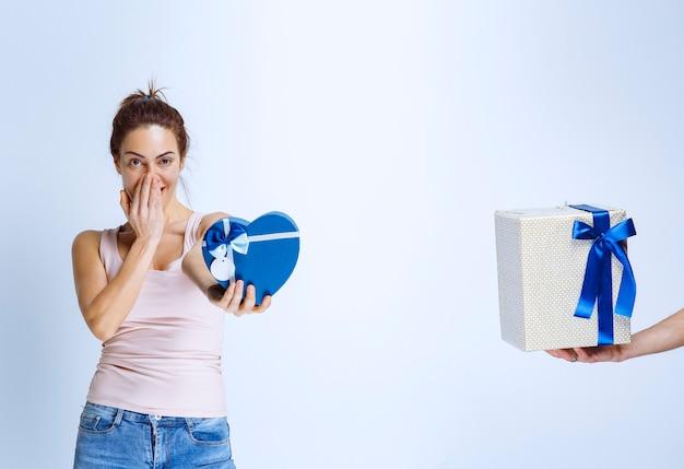 Junge frau hat eine blaue geschenkbox in herzform und wird eine weitere weiße geschenkbox angeboten