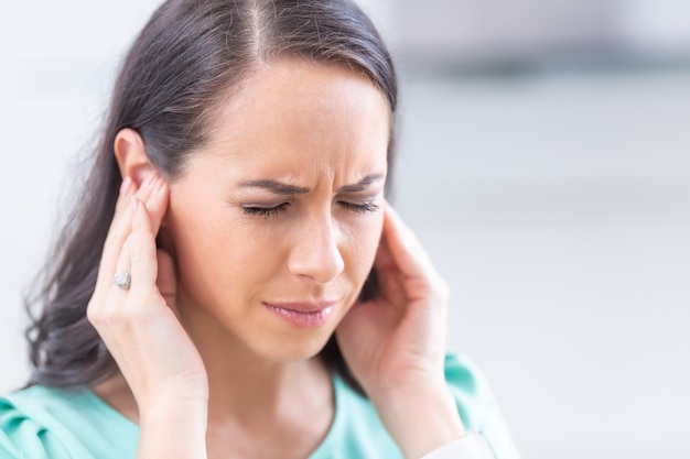 Junge frau hat kopfschmerzen, migräne, stress oder tinnitus - geräusch, das in ihren ohren pfeift.