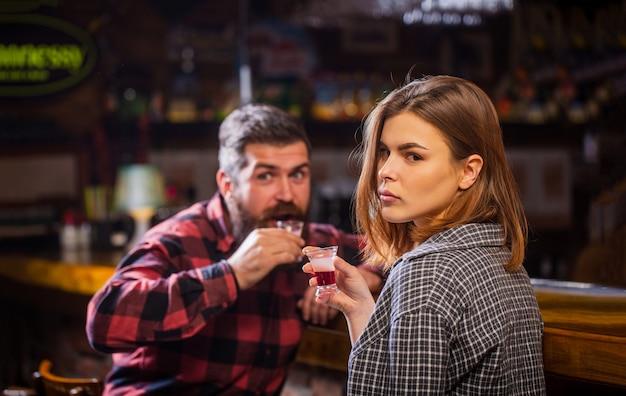 Junge frau hat probleme mit alkohol. weiblicher männlicher alkoholismus. alkoholismus bei frauen und männern. junger mann, der alkohol trinkt. alkoholisches getränk der frau in der bar.