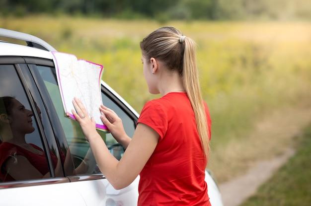 Junge frau hat sich auf dem feld verirrt, während sie ein auto fuhr und eine papierkarte las