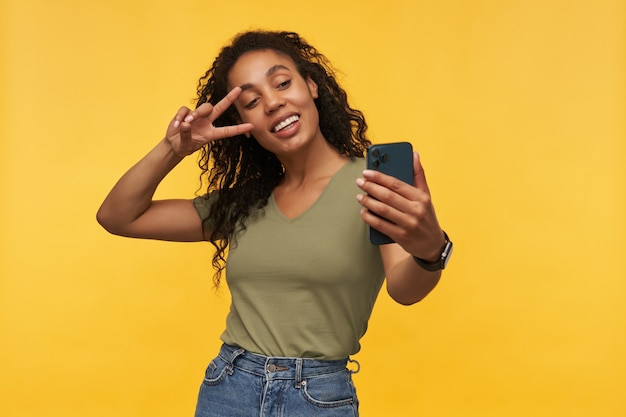 Junge frau hat video-chat mit ihrem freund, zeigt v-zeichen, lächelt breit und fühlt sich glücklich und zufrieden