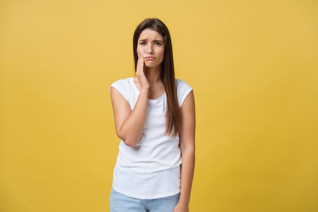 Junge frau hat zahnschmerzen, studiofoto, das auf einem gelben hintergrund lokalisiert wird