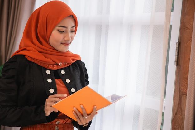 Junge frau hijab hält und schaut ein buch in der nähe von fenstern