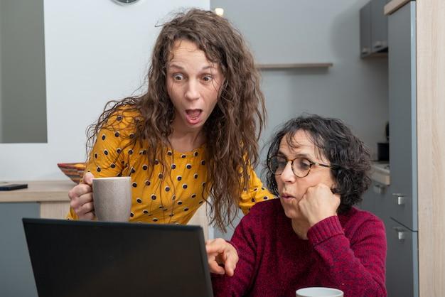 Junge frau hilft senior auf laptop-computer