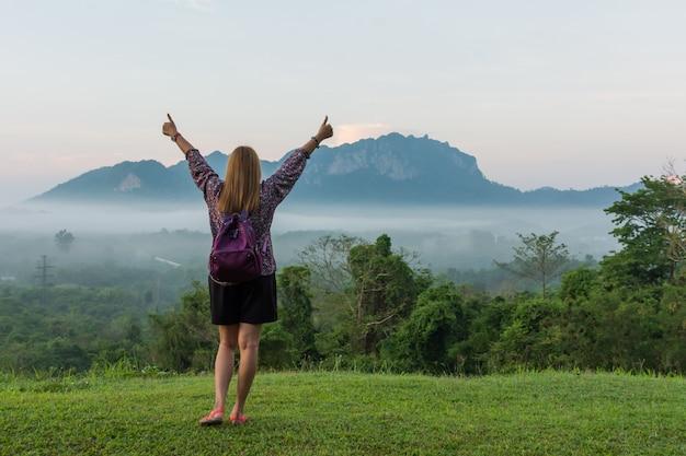 Junge frau hob hände morgens mit schönen bergen und seewolken an