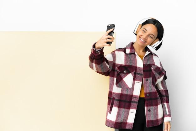 Junge frau hört musik mit einem großen leeren plakat isolierten hintergrund und macht ein selfie