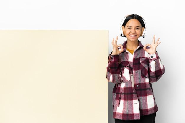 Junge frau hört musik mit einem großen leeren plakat über isoliertem hintergrund, das mit zwei händen ein ok-zeichen zeigt