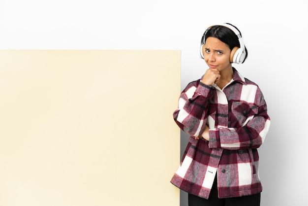 Junge frau hört musik mit einem großen leeren plakat über isoliertem hintergrund und hat zweifel