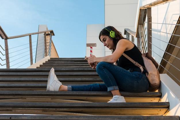 Junge frau hört musik mit ihren kopfhörern