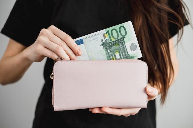 Junge frau holt geld aus einer lederbrieftasche heraus