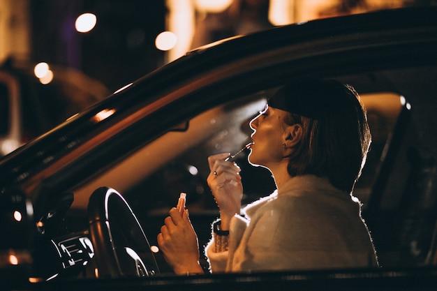 Junge frau im auto, das einen autospiegel untersucht