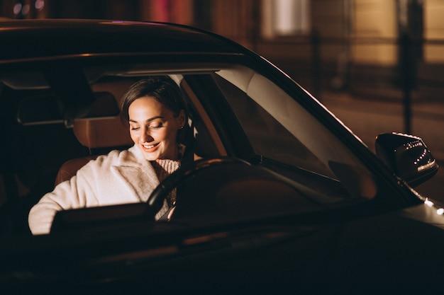 Junge frau im auto, das sicherheitsgurt hält
