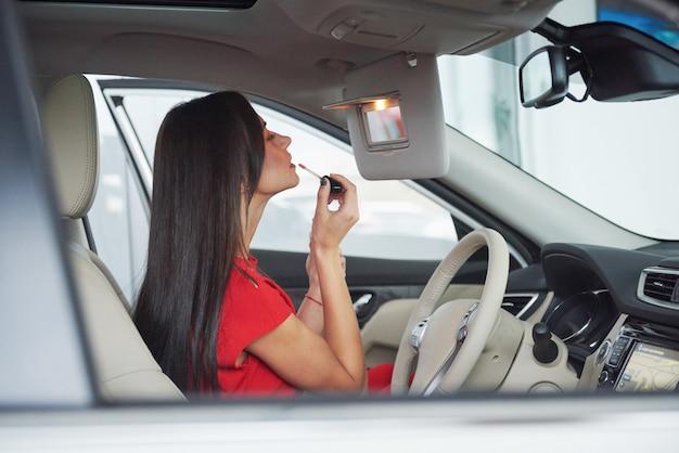Junge frau im auto, die lippenstift anwendet