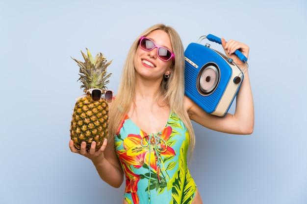 Junge frau im badeanzug, der eine ananas mit sonnenbrille und einem radio hält
