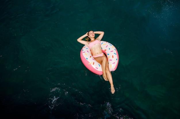 Junge frau im badeanzug schwimmt auf einem aufblasbaren ring im meer. sommerferienkonzept.