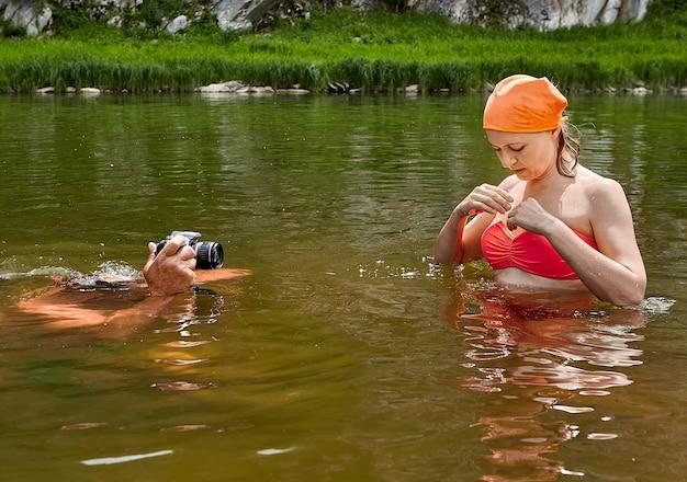 Junge frau im badeanzug und im orangefarbenen kopftuch steht im fluss und weißer mann fotografiert mit ihr darin mit wasserdichter kamera.