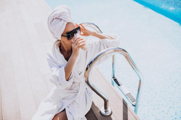 Junge frau im bademantel, die kaffee durch den pool trinkt