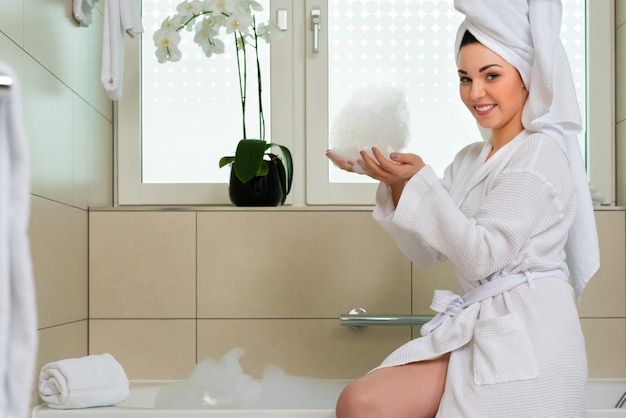 Junge frau im bademantel im hotelbadezimmer