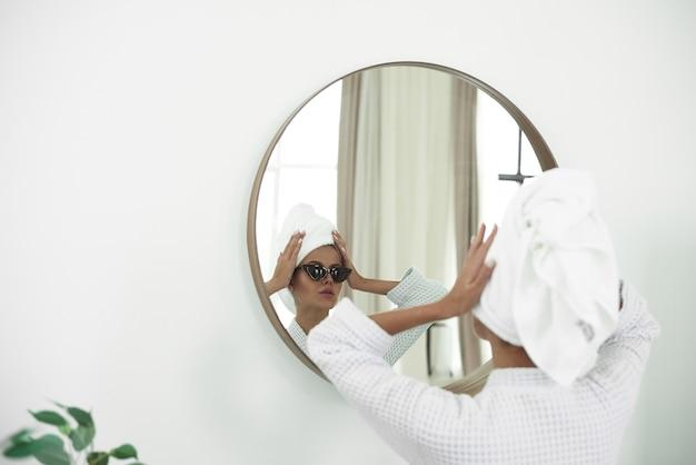 Junge frau im bademantel mit einem weißen handtuch auf ihrem kopf und einer schwarzen sonnenbrille, die im badezimmerspiegel schaut
