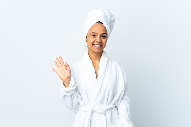 Junge frau im bademantel über isolierter weißer wand, die mit hand mit glücklichem ausdruck salutiert