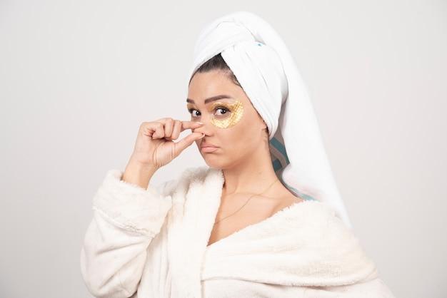 Junge frau im bademantel und in den kosmetischen augenklappen, die aufwerfen