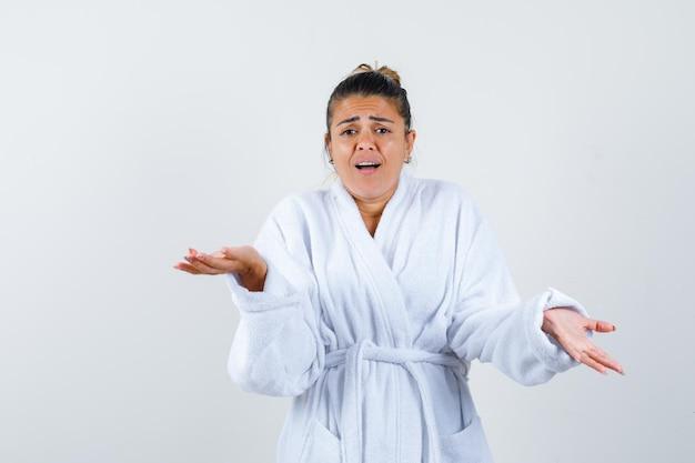 Junge frau im bademantel zeigt hilflose geste und sieht verwirrt aus looking