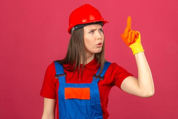 Junge frau im bauuniformhandschuhen und im roten sicherheitshelm, der neue idee steht und mit dem finger auf dunkelrosa hintergrund zeigt