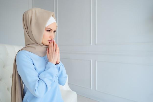 Junge frau im beige hijab und in den traditionellen kleidern, die beten