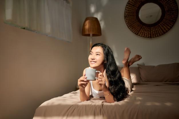 Junge frau im beigen pyjama, die zu hause auf dem bett liegt. entspannende und trinkende tasse heißen kaffee oder tee.