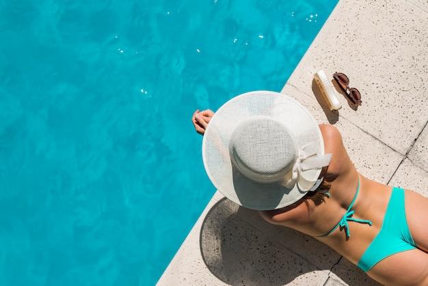 Junge frau im bikini, der auf poolside ein sonnenbad nimmt