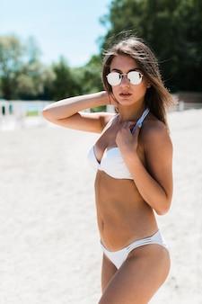 Junge frau im bikini, der kamera betrachtet