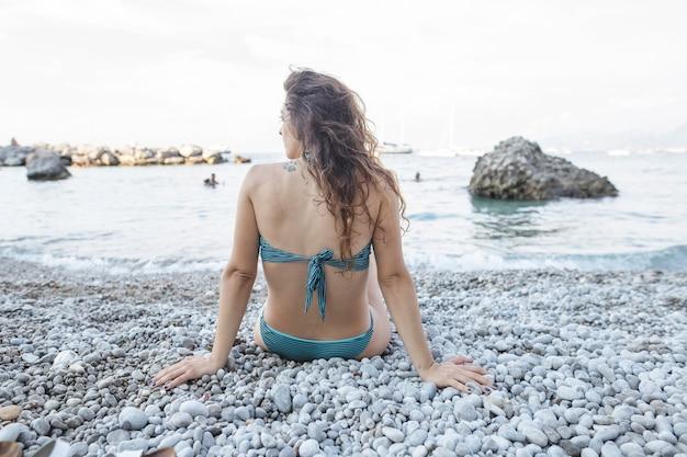 Junge frau im bikini, der nahe küste am strand sitzt