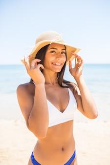 Junge frau im bikini, die weißen strohhut trägt und sommerferien am strand genießt. porträt der schönen lateinamerikanischen frau, die am strand mit sonnenbrille entspannt.