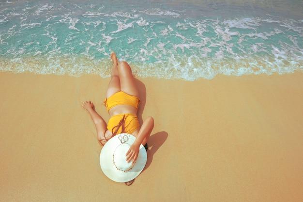 Junge frau im bikinilügen nehmen auf einem tropischen strand ein sonnenbad
