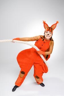Junge frau im bild des roten eichhörnchens, das ein seil zieht