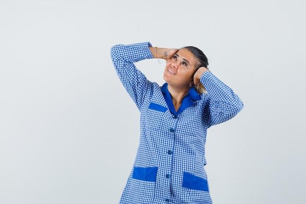 Junge frau im blauen gingham-pyjamahemd, das hände auf ohr drückt und hübsch, vorderansicht schaut.